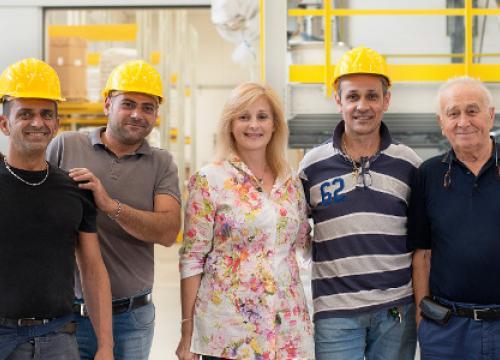 un gruppo di lavoratori in azienda indossano i dpi
