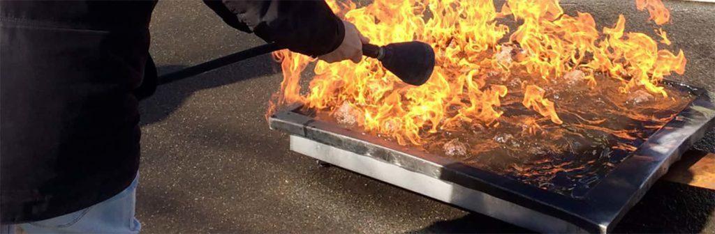uomo con estintore spegne un fuoco
