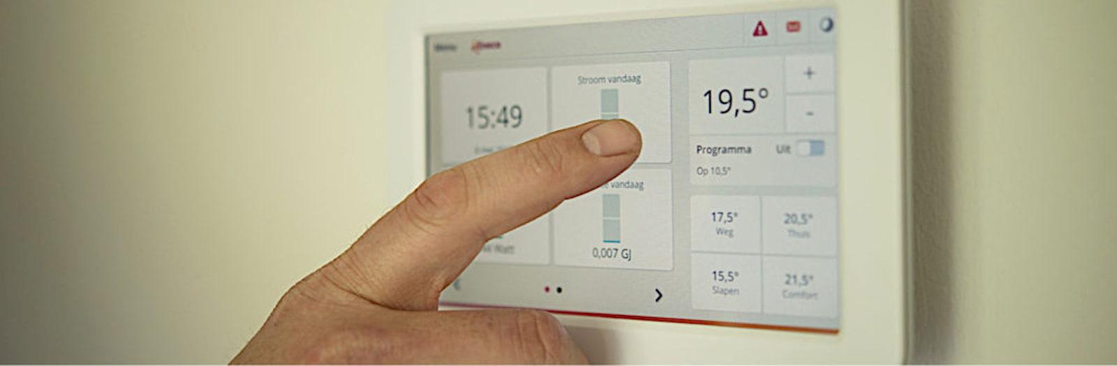 dito che tocca un climatizzatore touch per cambiare la temperatura