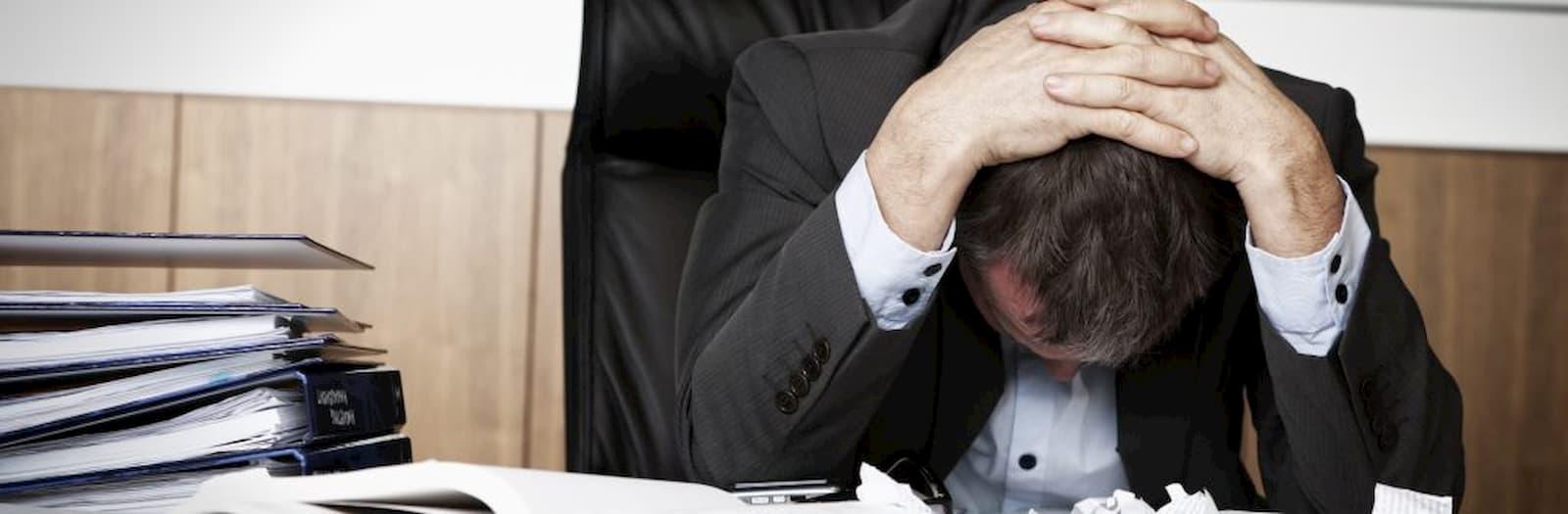 lavoratore stressato si mette le mani fra i capelli
