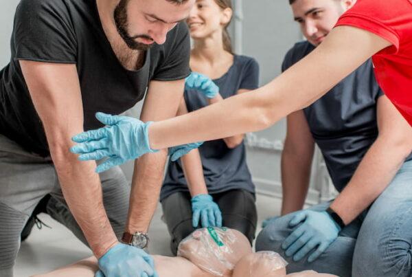 istruttore primo soccorso insegna massaggio cardiaco ad un corsista con un manichino